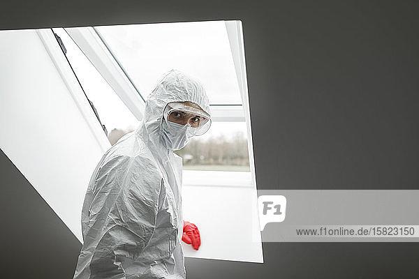 Mann in Schutzkleidung  am Fenster stehend