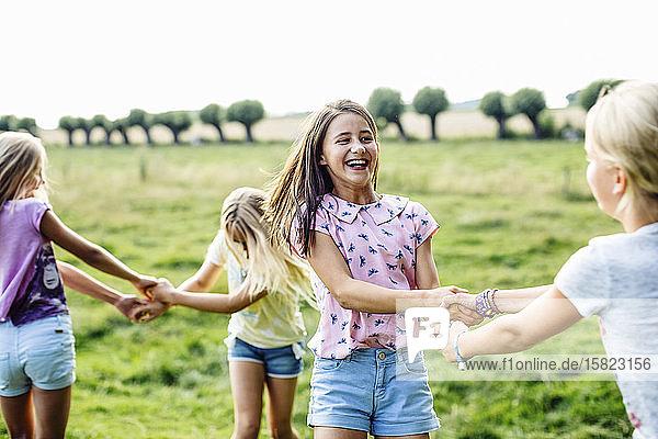 Glückliche Mädchen tanzen gemeinsam auf einem Feld Glückliche Mädchen tanzen gemeinsam auf einem Feld