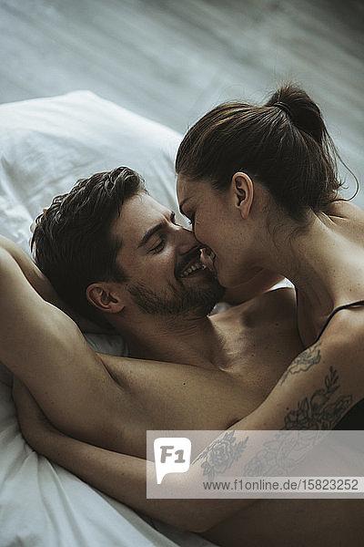 Glückliches Liebespaar im Bett