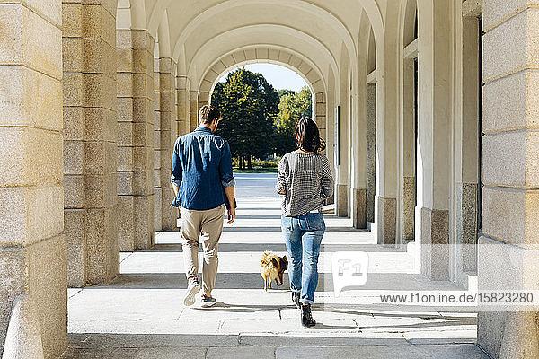 Rückansicht eines jungen Paares beim Spaziergang mit Hund in einer Spielhalle Rückansicht eines jungen Paares beim Spaziergang mit Hund in einer Spielhalle