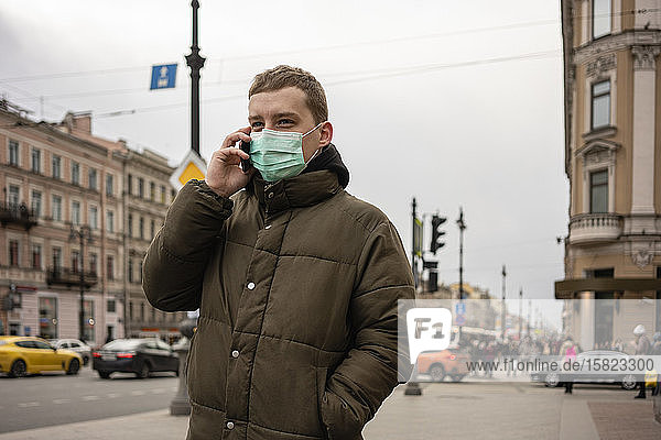 Young man with face mask  commuting in the city  St. Petersburg  Russia