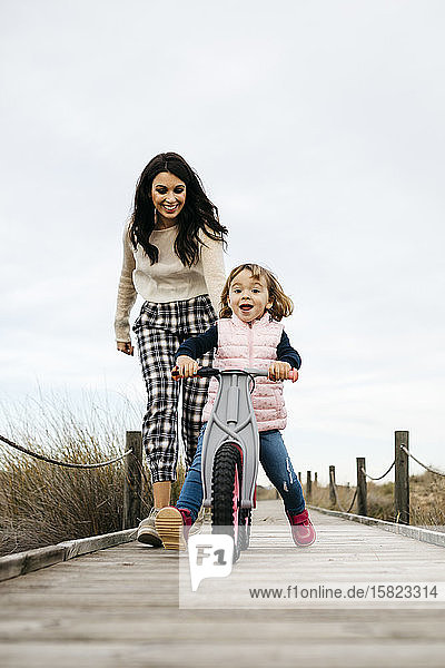 Mother and daughter with balance bicycle on a boardwalk in the countryside