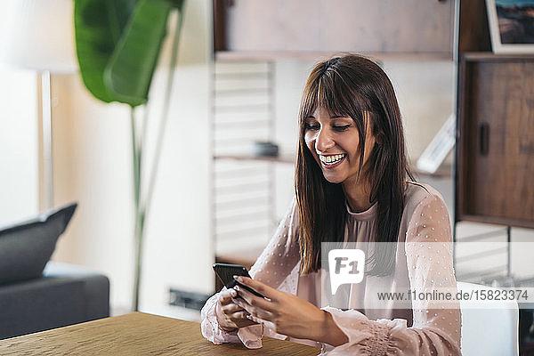 Glückliche junge Frau benutzt Mobiltelefon zu Hause