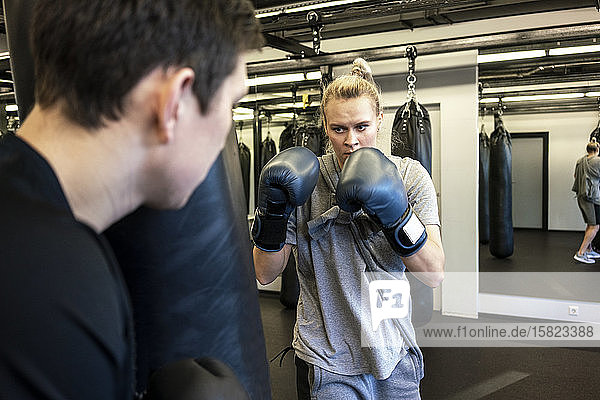 Coach and female boxer practising at sandbag in gym
