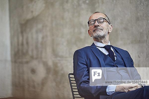 Leitender Geschäftsmann sitzt sitzend und entspannt mit geschlossenen Augen