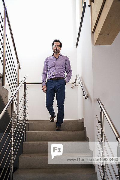 Geschäftsmann geht im Treppenhaus die Treppe hinunter