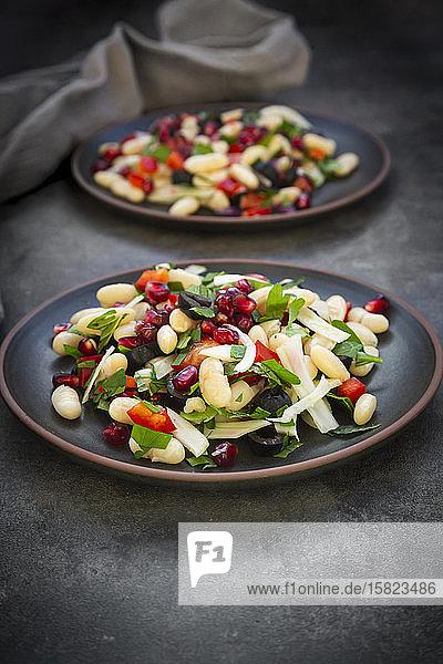 Zwei Teller Cannellini-Bohnensalat mit Fenchel  Paprika  schwarzen Oliven  Granatapfelkernen  Minze und Petersilie
