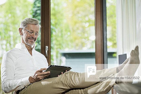 Lächelnder älterer Mann mit grauen Haaren in modernem Design-Wohnzimmer auf der Couch sitzend