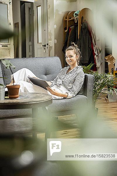 Junge Frau sitzt zu Hause auf dem Sofa und benutzt ein digitales Tablett