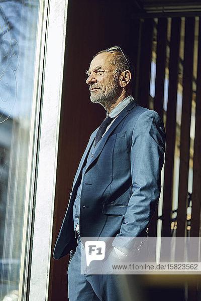 Leitender Geschäftsmann steht in seinem nachhaltigen Büro und schaut aus dem Fenster