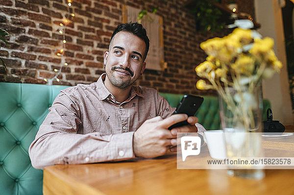Lächelnder Mann in einem Cafe mit Handy