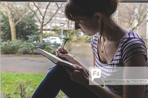 Frau sitzt vor der Fensterscheibe und zeichnet im Skizzenbuch
