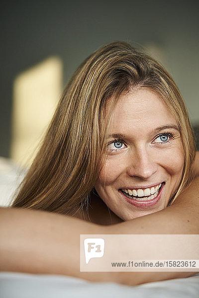 Porträt einer glücklichen blonden jungen Frau im Liegen