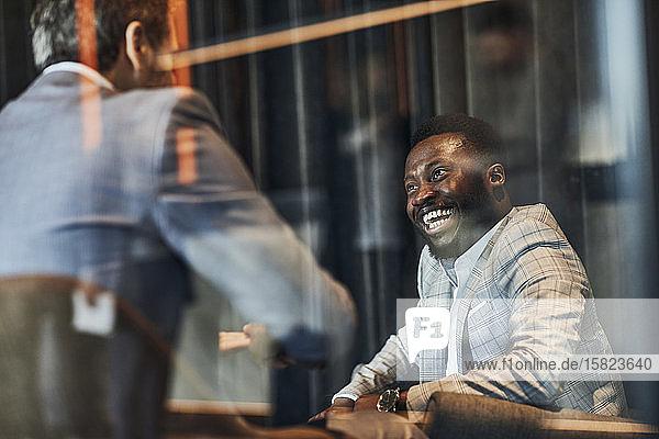 Lachende Geschäftsleute treffen sich in der Hotellobby