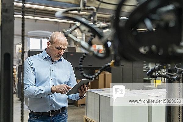 Geschäftsmann mit Tablette in einer Fabrik
