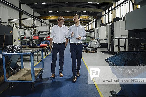 Zwei Männer gehen und sprechen in einer Fabrik