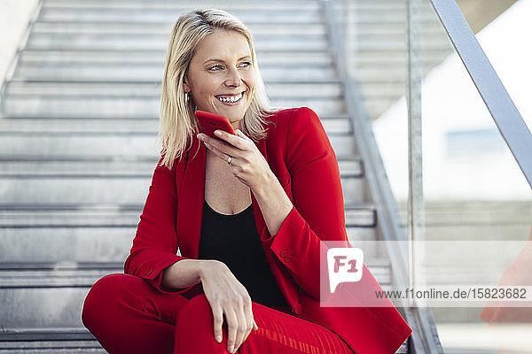 Blonde Geschäftsfrau in rotem Anzug und mit Freisprechtelefon  auf der Treppe sitzend