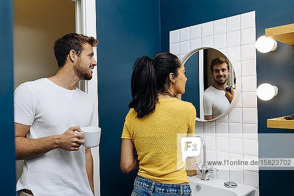 Lächelnder junger Mann schaut seiner Freundin beim Schminken zu Lächelnder junger Mann schaut seiner Freundin beim Schminken zu