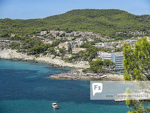 Spain  Balearic Islands  Camp de Mar  Coastal town in summer with forested hill in background