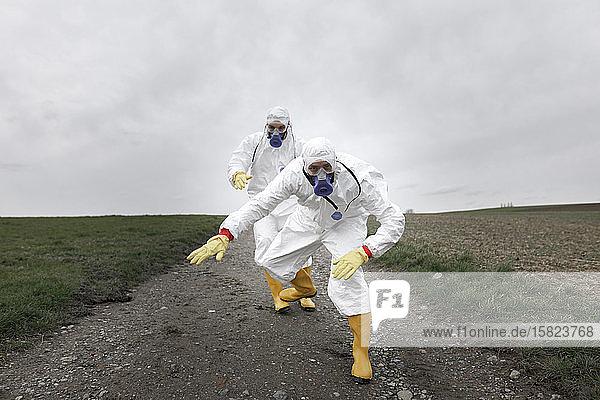 Wissenschaftler in Schutzkleidung  beim Springen und Tanzen auf dem Feld