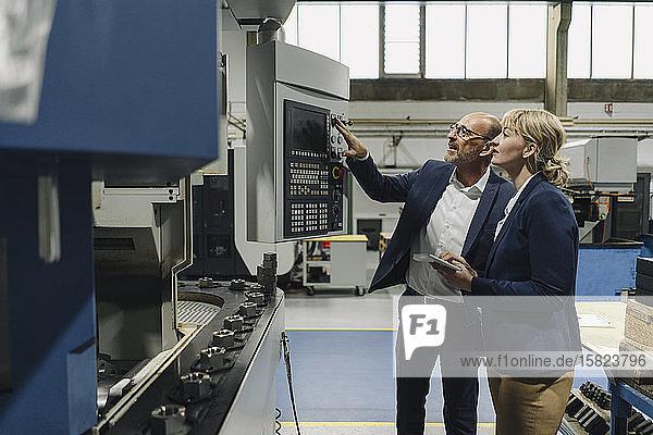 Ein Geschäftsmann erklärt einer Geschäftsfrau in einer Fabrik eine Maschine