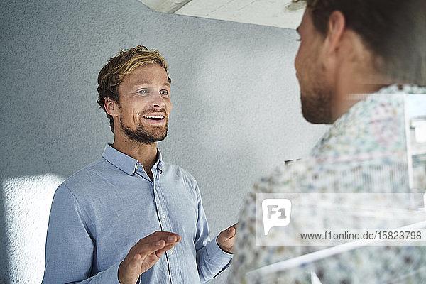 Zwei junge Geschäftsleute im Gespräch hinter einer Fensterscheibe
