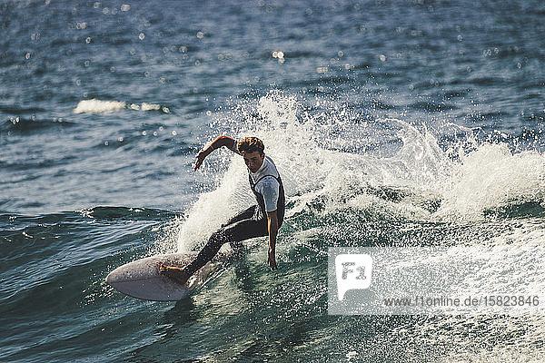 Jugendlicher surft im Meer