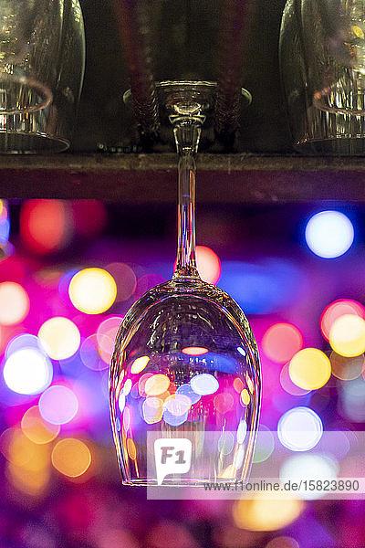 Leeres Weinglas hängt über der Theke mit Bokeh-Lichtern im Hintergrund
