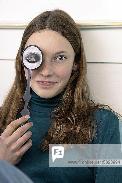 Portrait of smiling teenage girl with paper mask