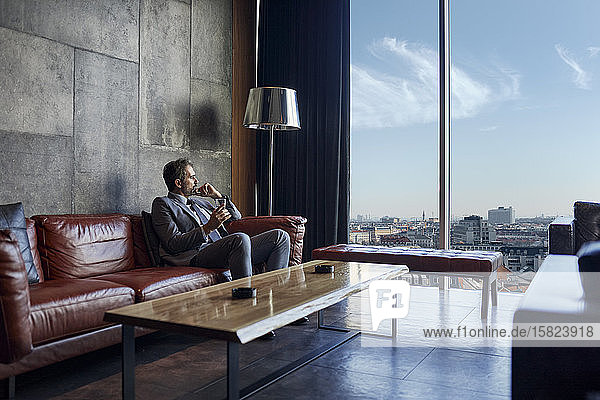 Businessman relaxing in hotel lobby looking out of window