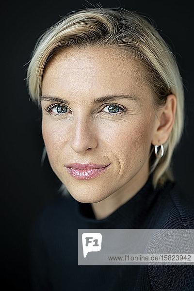 Porträt einer schönen Frau vor schwarzem Hintergrund  in die Kamera blickend