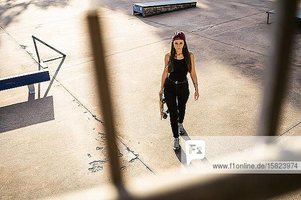 Junge Frau mit Skateboard im Skatepark