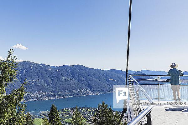 Wanderer steht auf der Aussichtsplattform Cardada oberhalb von Locarno mit Blick auf den Lago Maggiore  Tessin  Schweiz
