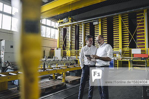 Zwei Geschäftsleute mit Tablette im Gespräch in einer Fabrik