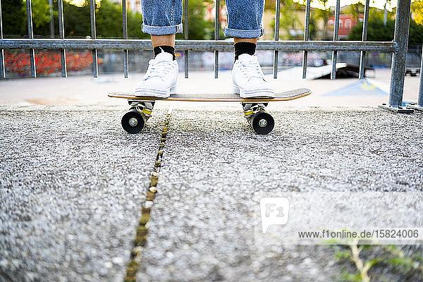 Junge Frau steht auf Skateboard