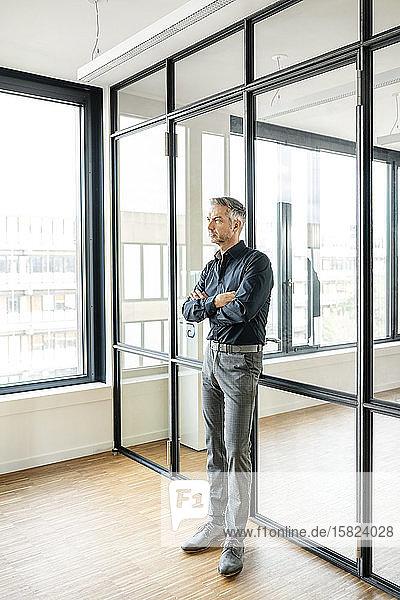 Geschäftsmann lehnt mit verschränkten Armen an Glaswand in seinem Büro