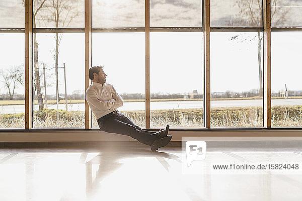 Geschäftsmann sitzt am Fenster im Großraumbüro
