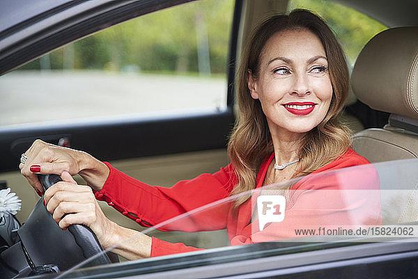 Porträt einer lächelnden reifen Frau beim Autofahren