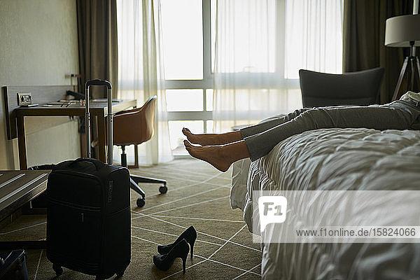 Beine einer Geschäftsfrau  die im Hotelzimmer auf dem Bett liegt