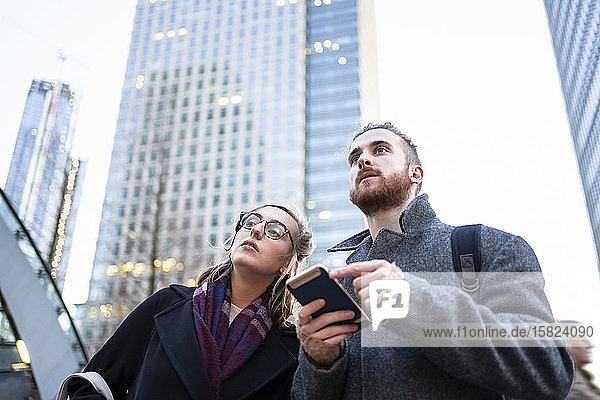 Junges Ehepaar mit Handy in der Stadt bei der Wohnungssuche  London  Großbritannien