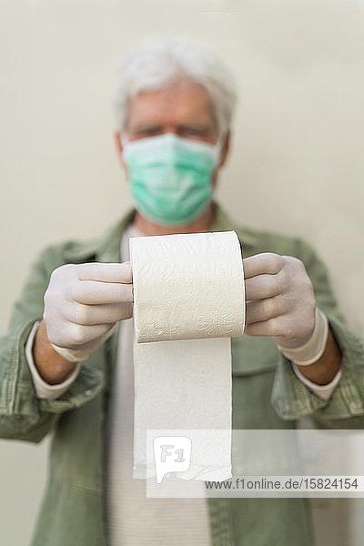 Mann mit Gesichtsmaske und Schutzhandschuhen  hält eine Rolle Toilettenpapier
