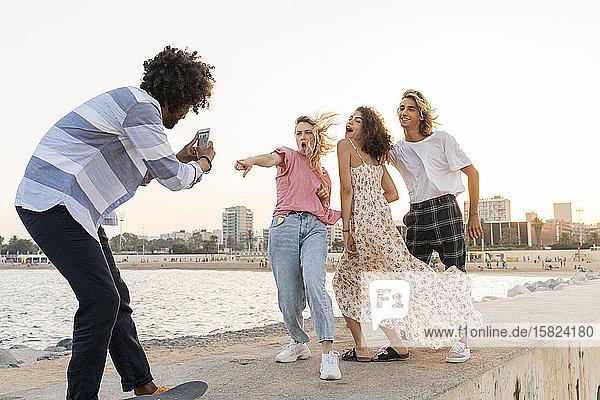 Glückliche Freunde posieren an der Kaimauer und machen ein Foto