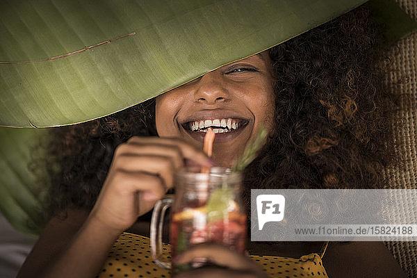 Nahaufnahme einer glücklichen Frau  die frischen Eistee trinkt