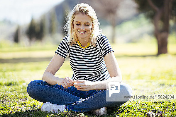 Blond lächelnde Frau sitzt auf einer Wiese in einem Park