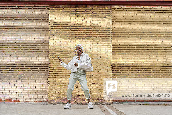 Frau  die mit Kopfhörern Musik hört und im Freien tanzt