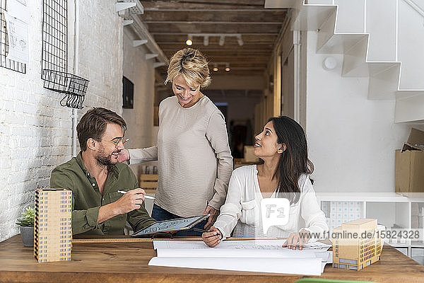 Lächelnde Kollegen arbeiten im Architekturbüro zusammen