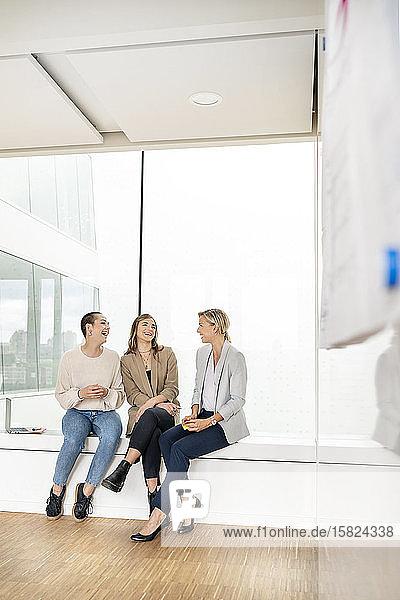 Geschäftsfrauen sitzen auf der Fensterbank im Bürogebäude  machen eine Pause  reden