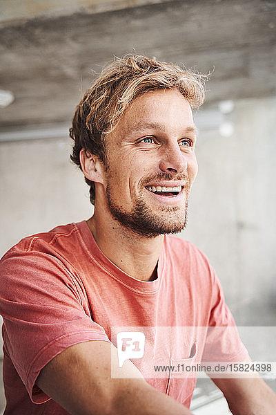Porträt eines lachenden jungen Mannes mit rotem T-Shirt