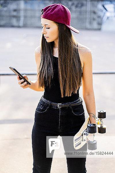Junge Frau mit Smartphone und Skateboard im Skatepark