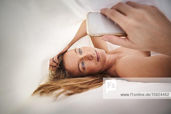 Blonde junge Frau liegt im Bett unter einer Decke und benutzt ein Mobiltelefon